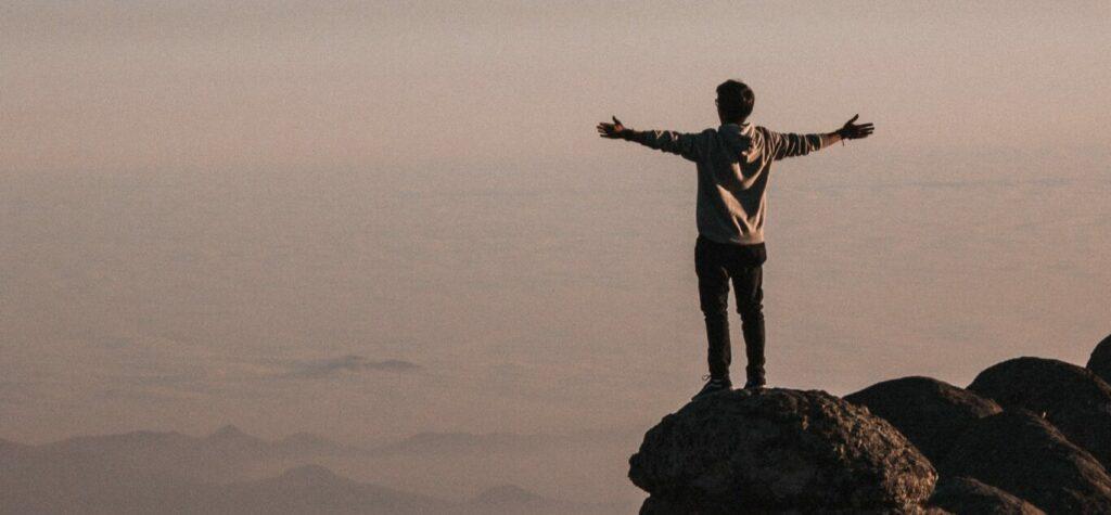 man-standing-beside-cliff