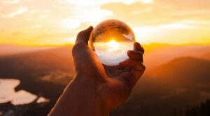 person-holding-glass-ball-reflecting-sun