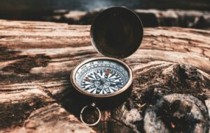 brass-colored-compass-on-brown-wooden-tree-stump-in-front-of-waterfalls-during-daytime