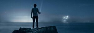 man-holding-flashlight-standing-on-rock
