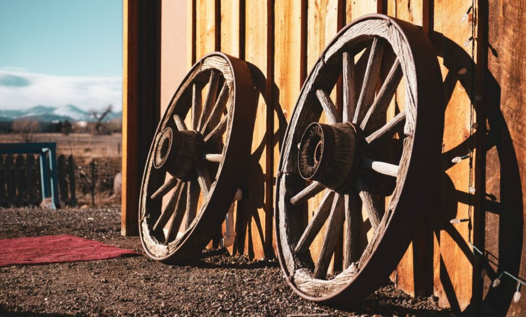 two-brown-carriage-wheels-leaning-on-brown-house