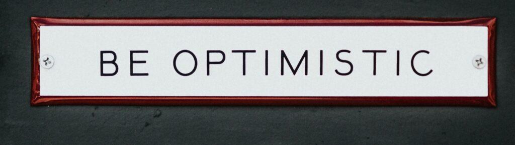 black-wooden-door-with-be-optimistic-text-overlay