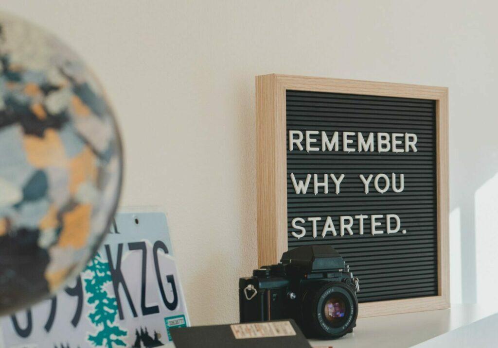 shallow-focus-photo-of black SLR camera on white wooden shelf