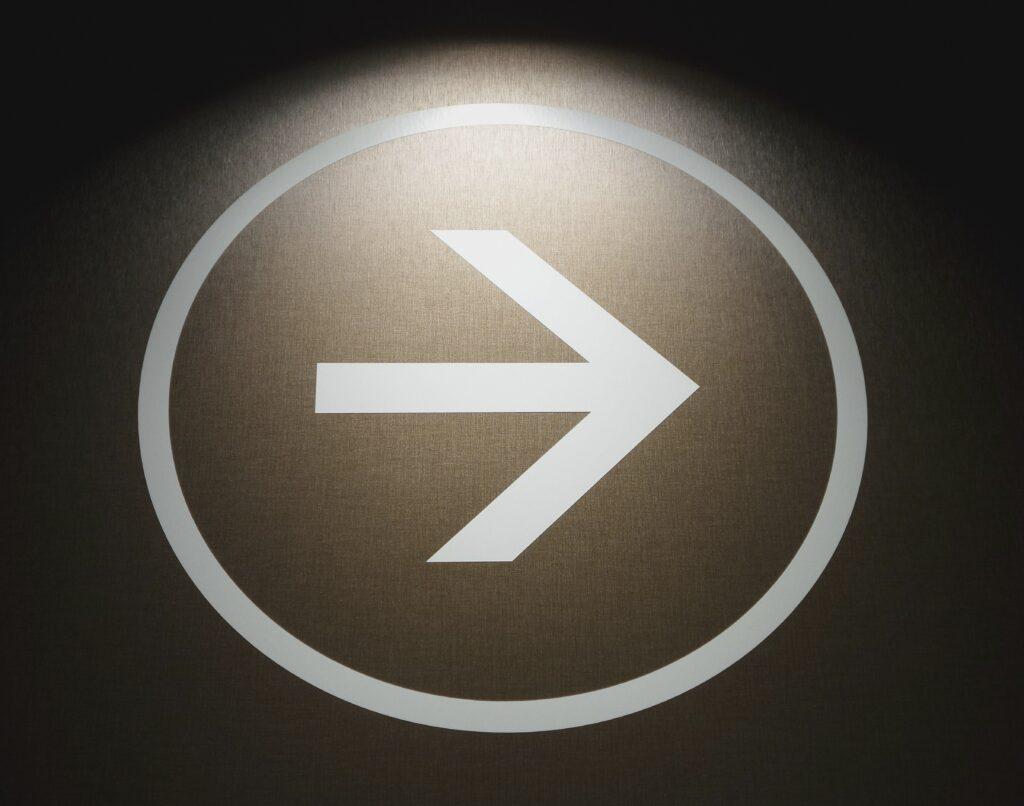 white-arrow-signage-on-black-wall
