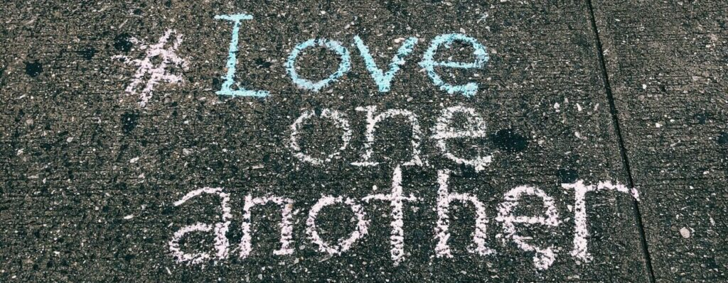 love-one-another-chalk-written-on-concrete