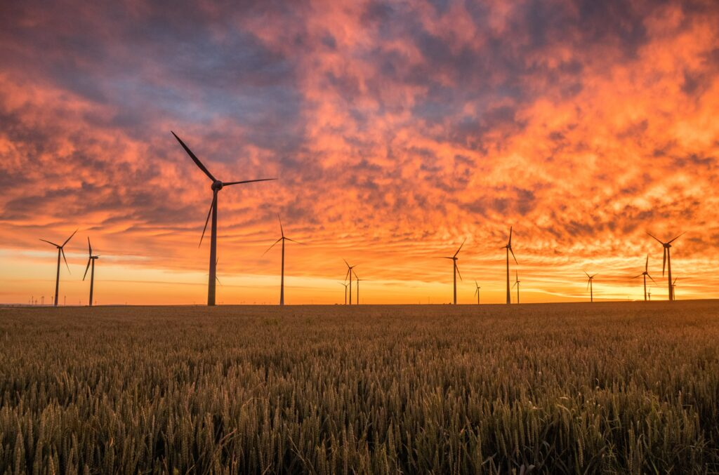 landscape-photography-of-grass-field-with-wind-turbines-under-orange-sunset