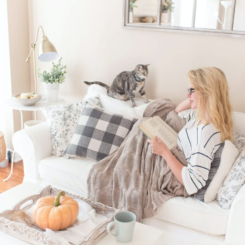 cat-on-couch-with-woman-reading-a-book